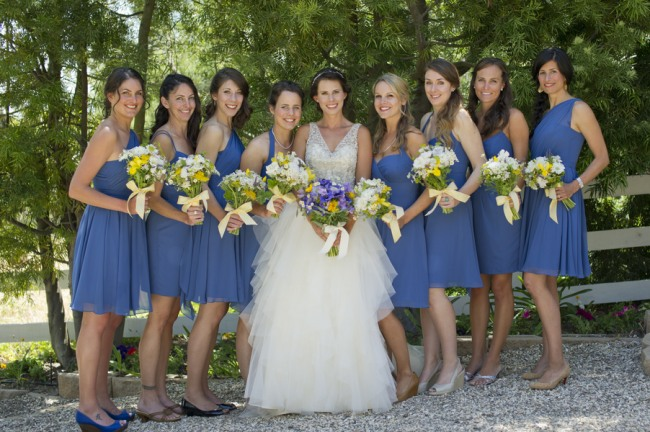 11 bride with bridesmaids in short blue dresses carrying yellow white and blue wild floral bouquet