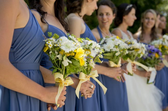 11 bridesmaids wearing blue dresses carrying white and yellow wild flowers with yellow ribbon