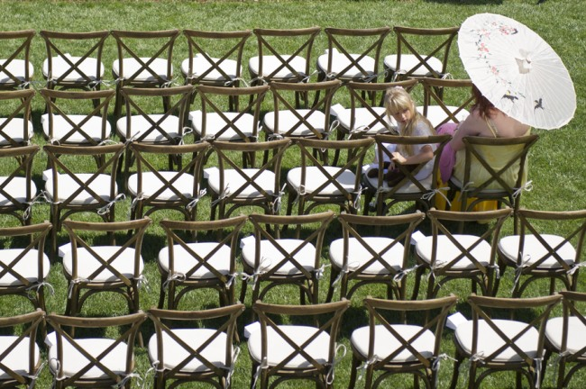 12 backyard wedding ceremony with wooden chairs and a women carrying a parasol