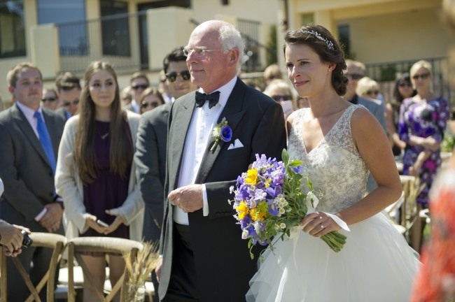 14 bride and father walking down aisle with blue white and yellow wild flower bouquet