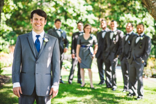 Groom wearing grey suit and blue neck tie at North Carolina Arboretum