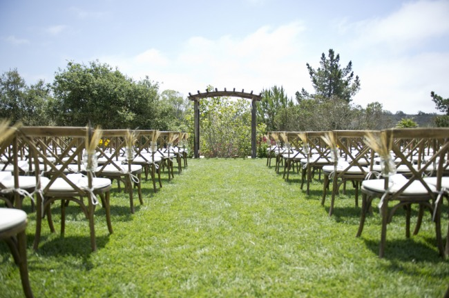 1Outdoor backyard ceremony with wooden chairs and arbor and mason jars with wheat