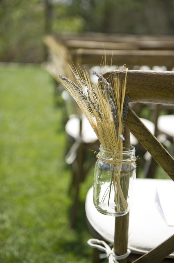 2 Outdoor backyard ceremony with wooden chairs and mason jars with lavender and wheat
