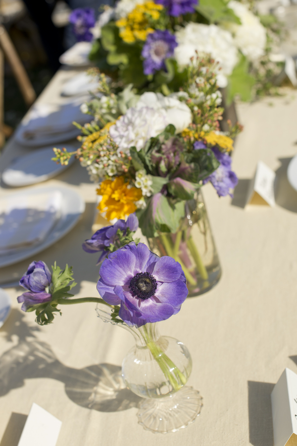 21 purple white and yellow wild flowers in vases for wedding reception
