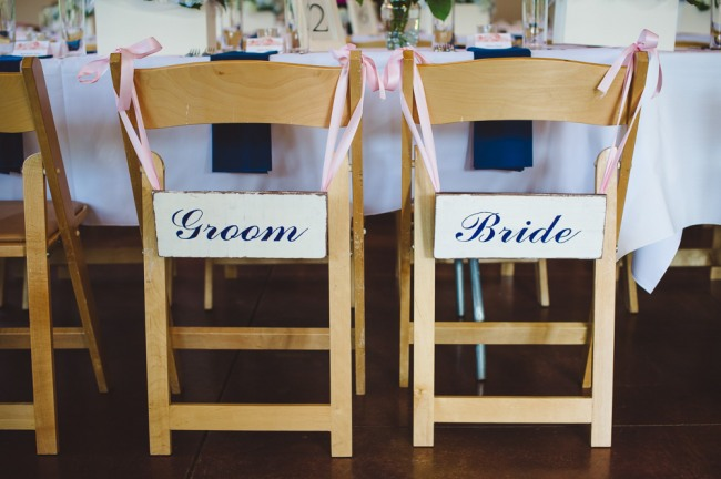 Pink and white bride and groom sign on wooden chair at pink and navy blue wedding reception at  at North Carolina Arboretum