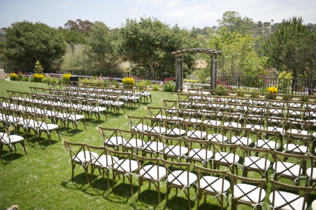 3 Outdoor backyard ceremony with wooden chairs and arbor and mason jars with wheat