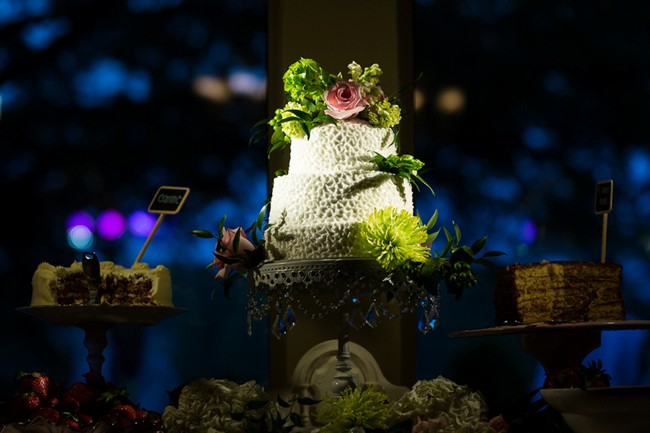 3 tier white wedding cake with green and pink flowers