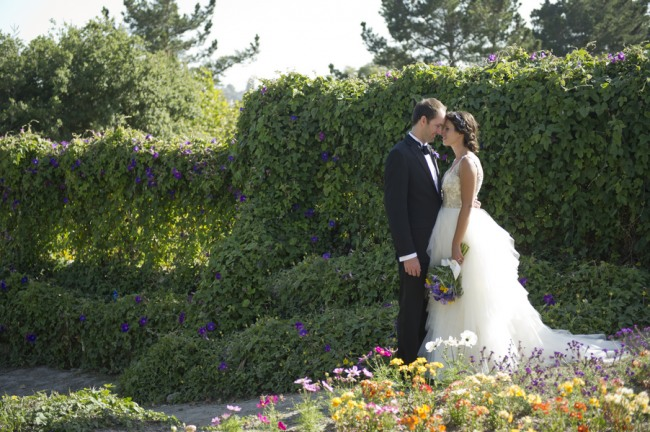 32 bride and groom kissing behind wild flower garden