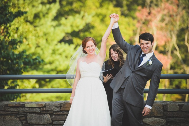 Bride and groom holding hands in the air after wedding ceremony at North Carolina Arboretum