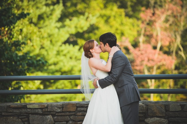 Bride and groom kissing  at North Carolina Arboretum