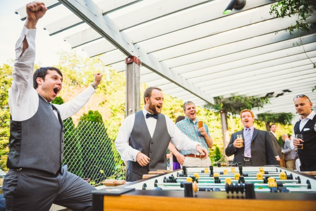 groom and groomsmen playing foosball  at North Carolina Arboretum