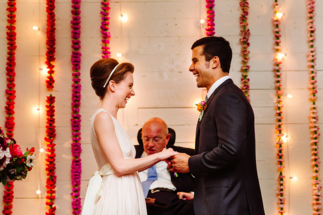 bride wearing blush pink dress and groom standing at altar at Palm Door with pink red and yellow floral backdrop