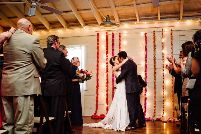 bride wearing blush pink dress and groom standing at altar at Palm Door with pink red and yellow floral backdrop kissing