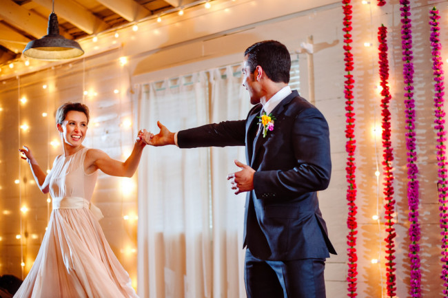 bride wearing blush pink dress and groom dancing at altar at Palm Door with pink red and yellow floral backdrop