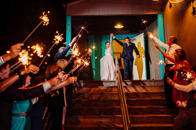 Bride and groom exiting wedding from Palm Door with sparklers