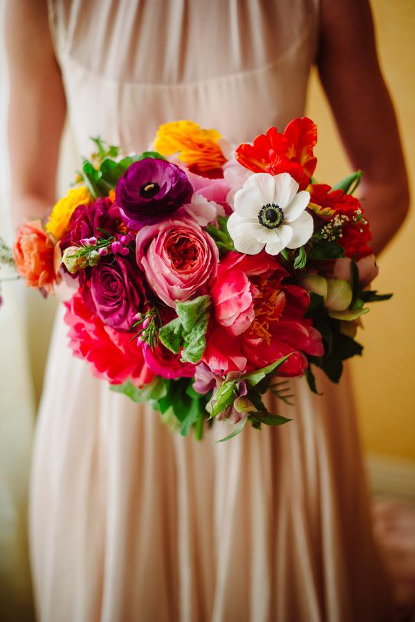 Bride in Blush pink dress carrying dahlias, anemonies, peonies, marigolds, wild roses bouquet   at Palm Door
