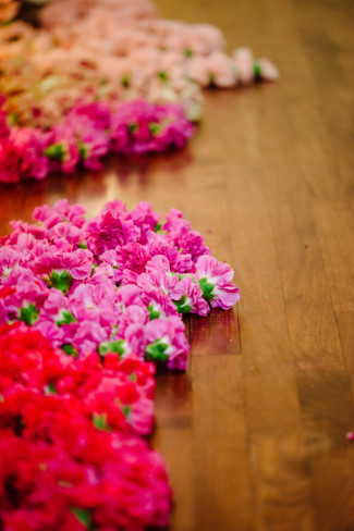 Pink and red carnations on the floor at wedding ceremony at  Palm Door venue
