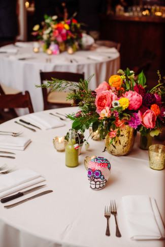 Day of the Day themed Wedding reception at Palm Door with pink yellow green flowers  colorful paper mache skull