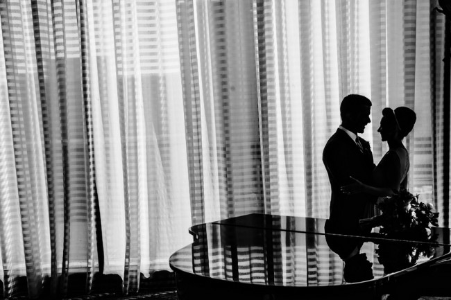 Bride and groom standing before a grand piano before wedding ceremony