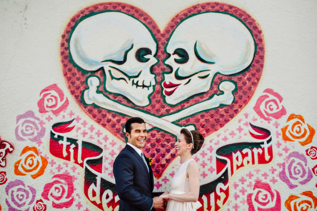 bride wearing blush pink dress and groom standing in front of wall with skulls