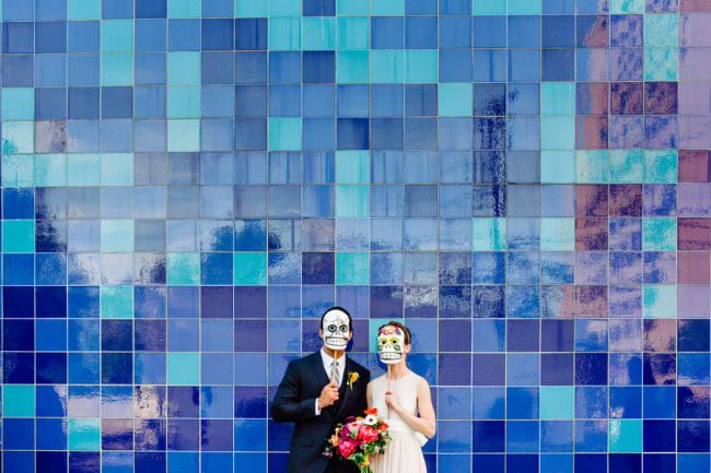 bride wearing blush pink dress with groom standing in front of blue tile wall wearing day of the dead masks