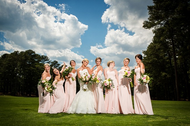 Bride and bridesmaids with long pink skirts and green white and pink bouquets