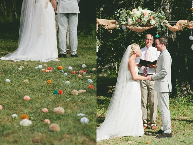Bride and groom at altar with pom pom decor lining the ground and hanging in trees