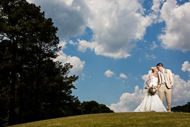 Bride and groom kissing with bright blue sky in the back ground
