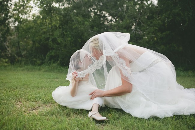 Bride with flower girl on grass under veil