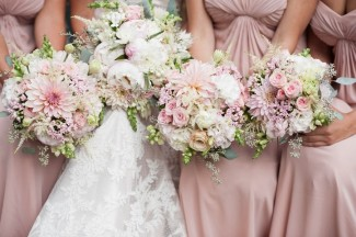 3 bridesmaids wearing pink dresses with bride all holding pink, purple and white bouquets