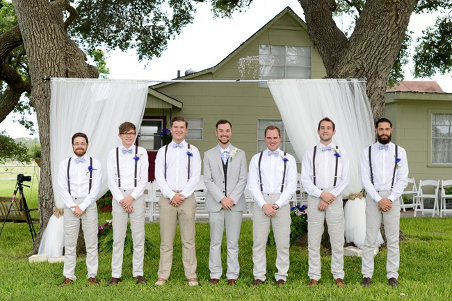 Groom and groomsmen in bow ties and suspenders and blue boutinieres
