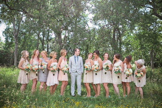 Groom with bridesmaids in mismatched dresses