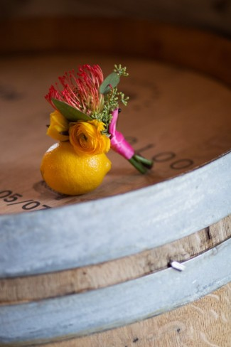 Boutinnere and whole lemon on wine barrel