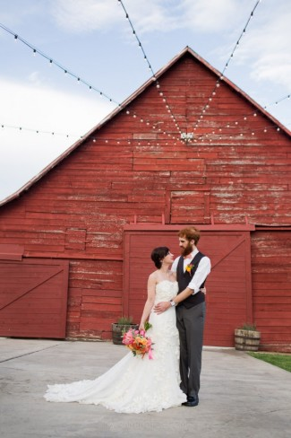 Bride and groom under lights in front of dusty red barn