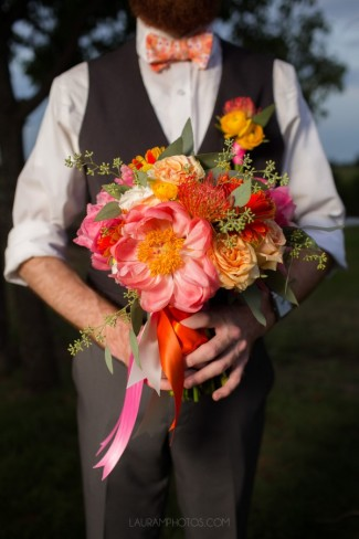groom holds colorful bouquet