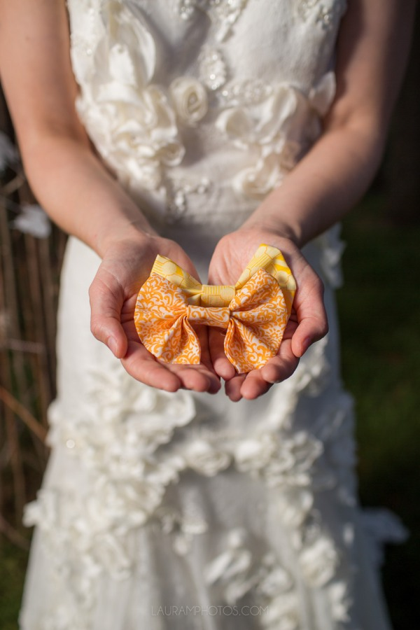 bride holding lemon and apricot color bowties