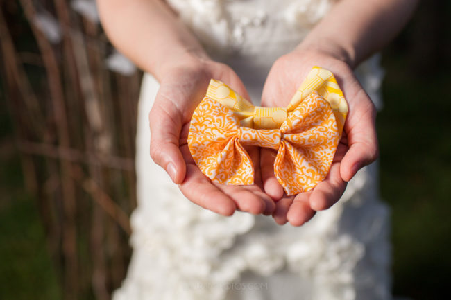 Bride holding orange and yellow paisley pattern Bow ties
