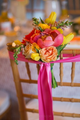 floral arrangement and pink streamer on chair