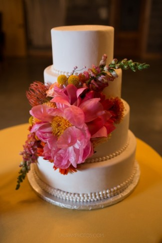 4-tier white wedding cake with giant pink flower accent and white beads