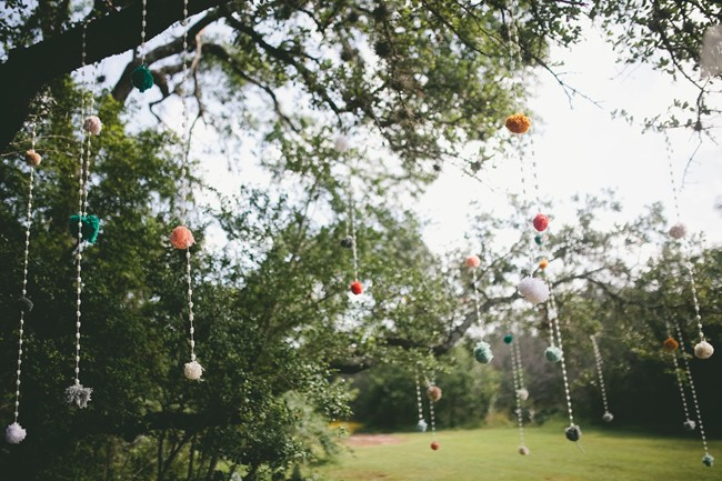 Wedding ceremony crystals hanging from tree with pom pom