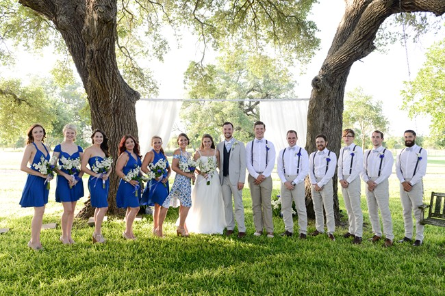 Wedding party in white and blue standing infront of trees