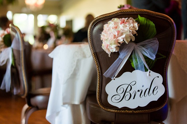 Wedding reception chair with bride sign and white pink hydrangea