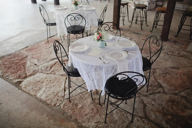 black rod iron bistro table for wedding reception with lace table cloth and white hydrangea