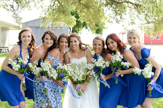 Bride And Bridesmaids In Blue Dresses Holding White Bouquets With Ribbon