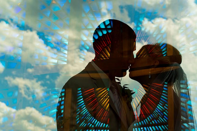 bride and groom kissing and shadowed out with blue sky and clouds in background with stain glass window