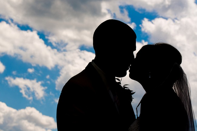 bride and groom kissing and shadowed out with blue sky and clouds in background
