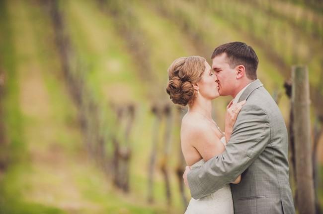 bride and groom kissing in vinyard