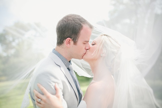 bride and groom kissing under wedding veil