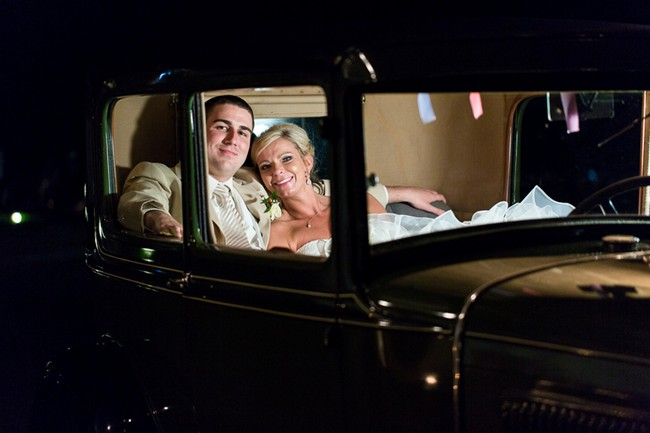 bride and groom leaving wedding reception in a green vintage car