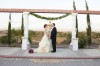 bride and groom standing at altar at Mount Palomar Winery with peach rose petals and fountain